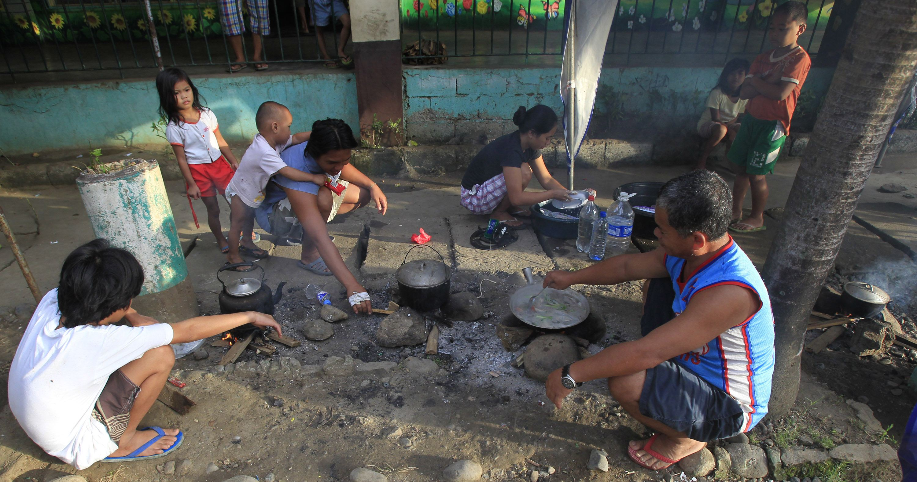 Homeless Typhoon Washi survivors cook their meal on school grounds in Cagayan de Oro