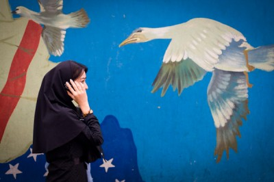 File photo of a woman talking on her mobile phone while passing mural on wall of former U.S. embassy in Tehran