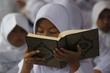 A girl practices reading the Koran in Jakarta. More than 1,400 children gathered at a park in Indonesia to read the Koran to mark the holy month of Ramadan, which start Friday. (Photo from REUTERS/Supri)