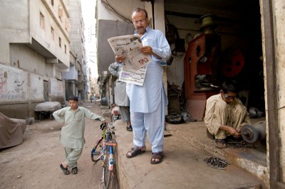 A small business owner in Karachi reads a morning newspaper. News in Pakistan tends to focus on international affairs at the expense of local problems. (Photo by Alex Stonehill)