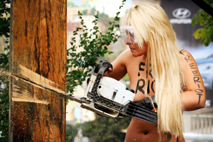An activist from women's rights group Femen uses a chainsaw to cut down a Christian cross near the Oktyabrsky Palace in central Kiev