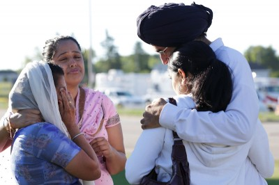 Mourners cry outside the scene of a mass shooting at a Sikh Temple in Wisconsin. The shooter used a legally purchased 9mm handgun in the rampage. (Photo from REUTERS/John Gress)