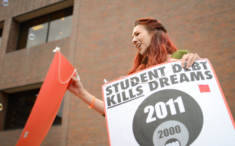 Brandi Finn, a student at Seattle Central Community College, hands out signs for the Student Debt Noise Brigade protest on Wednesday, August 8. (Photo by Hallie Golden)
