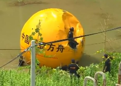 While you're toasting the end of the world tonight in Seattle, a man in China is hiding out in a giant yellow ball. (Screenshot via youtube.com)