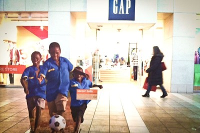 Kenyan children play with a donated soccer ball in part of the World Vision display at Northgate Mall. (Photo by Alex Stonehill)