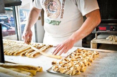 A baker at Piroshky Piroshky rolls together cinnamon cardamom braids. (Photo by Yvonne Rogell)