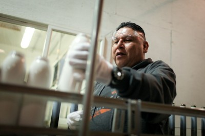 Tony Morales, a longtime employee, handles bottles on the line at Liberty. The company says they're able to compete with cheaper Chinese labor through advanced mechanization and lower shipping costs. (Photo by Alex Stonehill).