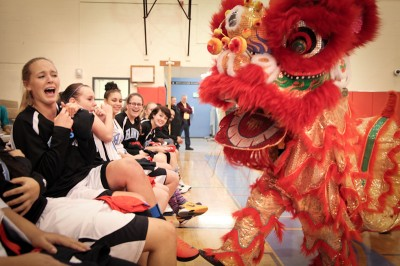 Chief Sealth Junior Allison Steele is teased by a Chinese Dragon during a performance from the David Leong Kung Fu studio. The dance opened an exhibition game between the Nankai High School and Chief Sealth girls basketball teams. (Photo by Alex Stonehill)