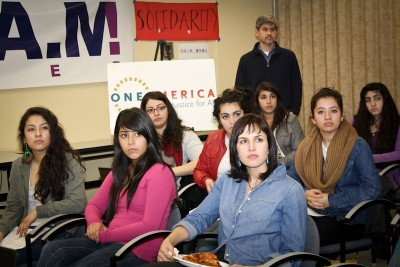 Jenesis Garcia (far left) and others watch the State of the Union address with some skepticism at a watch party held by SEIU and OneAmerica. (Photo courtesy OneAmerica)