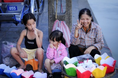 Family members sell floating lanterns on the waterfont in Hoi An, Vietnam. Cute kids can help boost sales, but in most cases they should be in school instead. (Photo by Marat Garafutdinov)