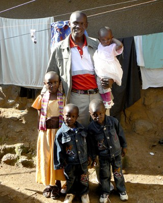 Jacktone Otieno (center) poses with his children (from left to right) Benta (11), Blesssing (3), Gift (3) and Abigail (1) outside of their home in Kibera. (Photo by Abby Higgins)