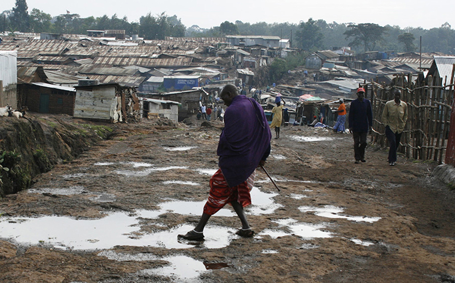 A Masai man cleans his shoe off in a puddle in Kibera. Masai, known to be fierce fighters, are often employed as personal bodyguards inside the slum to walk residents home late at night. (Photo by Alex Stonehill)