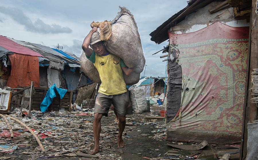 Near Jakarta, Indonesia, a man earns a daily wage picking through the Bantar Gebang landfill for recyclables to sell. Slum dwellers typically live a much more environmentally friendly lifestyle, finding value in what others would waste. (Photo by Branden Eastwood)