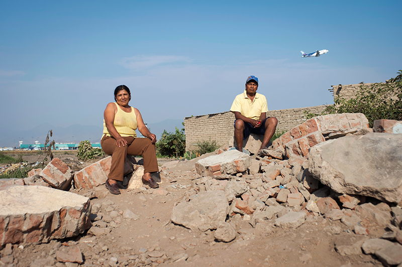 Catalina Guzman Harrimache and her husband Teofilo Huaman Loayza sit on the remnants of a home. The home had its own ground water supply that the town now frequents to wash clothes while sitting amidst the rubble. In the background the main terminal of Jorge Chavez International Airport can be seen. (Photo by Oscar Durand)
