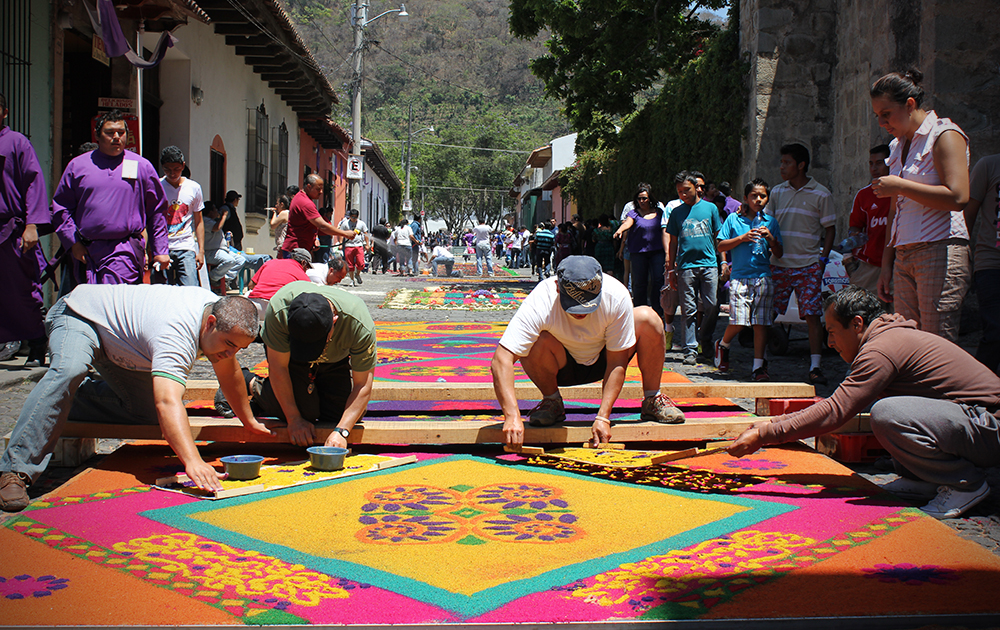 A team prepares a alfombra, or sand carpet, which take up to 10 hours to prepare the day of the parade. (Photo by Devin McDonald)