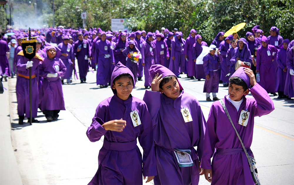 "Three youth participate in a Semana Santa procession, wearing the iconic purple robes and ""capirotes"" hoods. (Photo by Devin McDonald)"