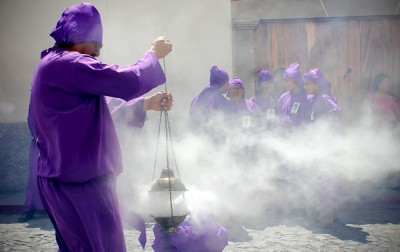 "A man releases a potent cloud from his ""incensario"" filled with myrrh resin and used to ""cleanse"" the parade route. (Photo by Devin McDonald)"