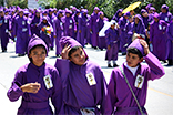 Three youth participate in a Semana Santa procession, wearing the iconic purple robes. (Photo by Devin McDonald)