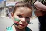 A young Syrian in Deraa, at a protest commemorating the massacre at Al-Houla last May, where over 100 women and children were allegedly killed by pro-government militias. (Photo by  Syrian Revolution Memory Project)