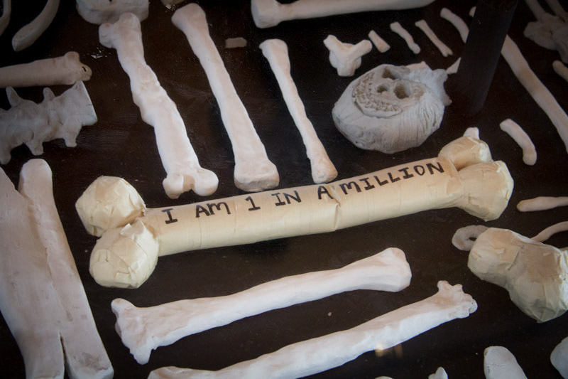 Replicas of human bones line the floor of [storefront] in Pioneer Square. (Photo by Christian Zerbel)