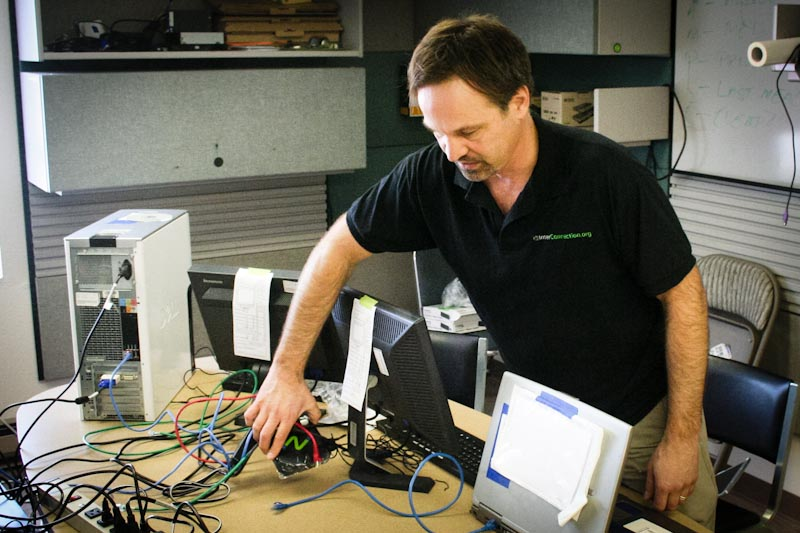 Charles Brannick, founder of InterConnection, works in a lab at the non-profit's headquarters on Stone Way N. A server box like the one seen, left, is capable of running virtual desktops for up to 20 monitors. (Photo by Chris Swanicke)