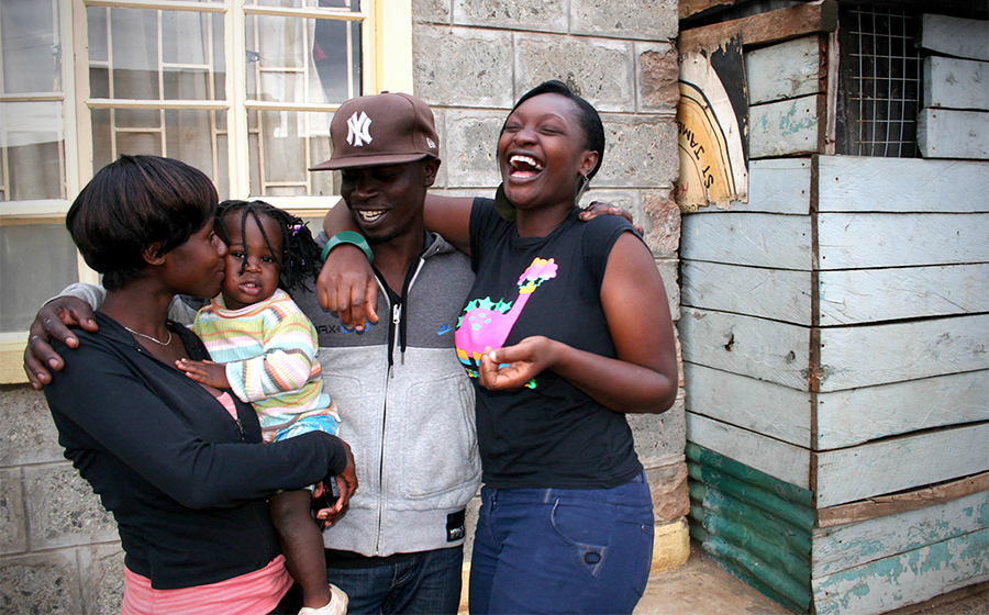 A family, Halima, Richie and Leslie (from left to right), hugs outside of their home in Kibera. Despite lack of access to government services, many residents in Kibera stay because of the strong community and support neighbors. (Photo by Abby Higgins)