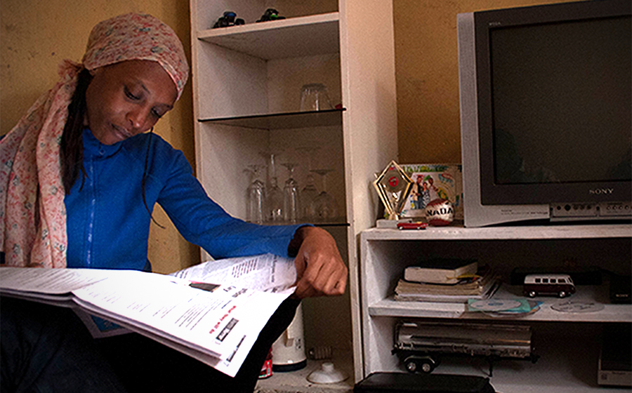 Mariam reads The Ghetto Mirror, a youth-produced newspaper, in her home in Kibera. (Photo by Abby Higgins)