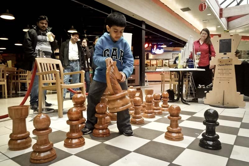 "Aavir, 6, plays with the over-sized chess set during ""2nd Saturday Family Night"" at Crossroads mall. (Photo by Ilona Idlis)"