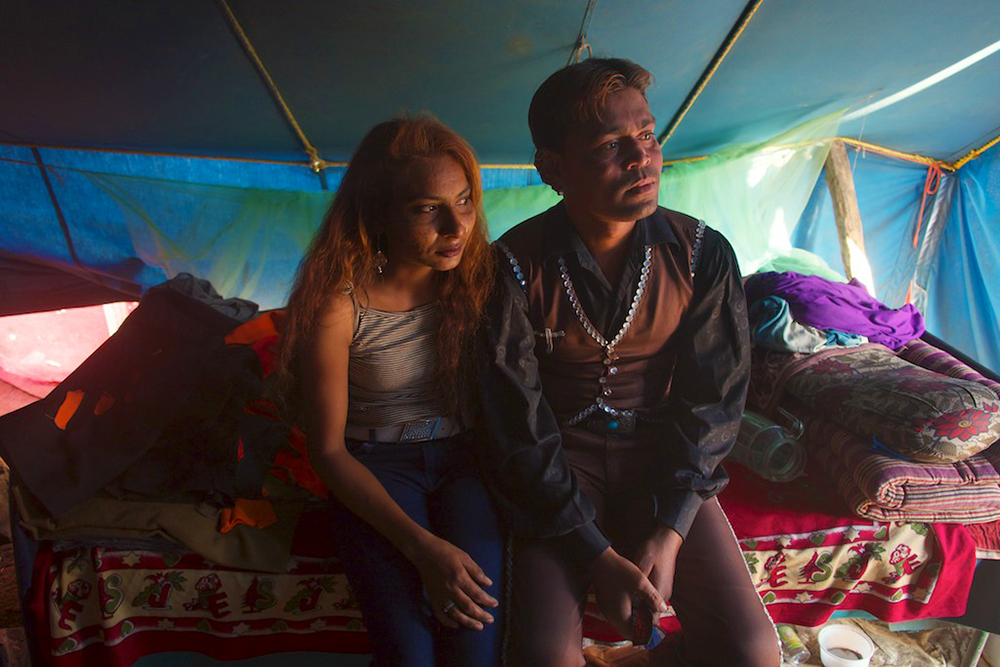 A couple, both circus performers, sit on their bed looking out of their tent.