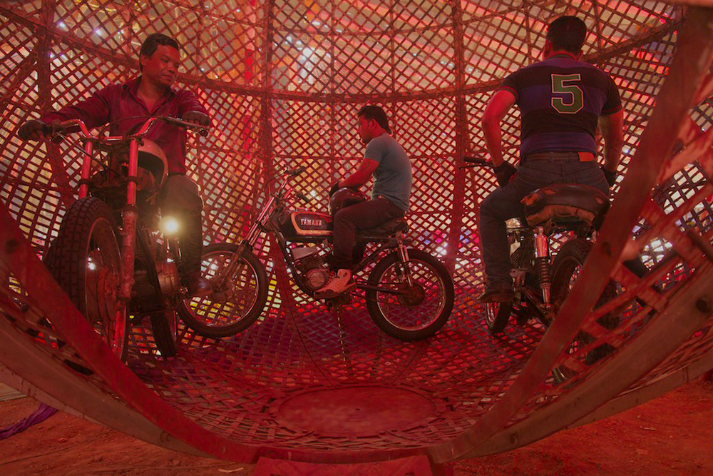 Bikers prepare to ride motorcycles inside a metal ball.