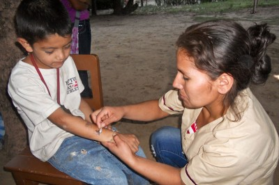 Marta, a health promoter with Etta Projects in Bolivia, cares for a local child. (Photo courtesy Etta Projects)