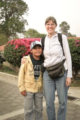 The author with Pedro wearing the gifts she brought: a Seattle Seahawks t-shirt and baseball cap. (Photo by Karen Story)