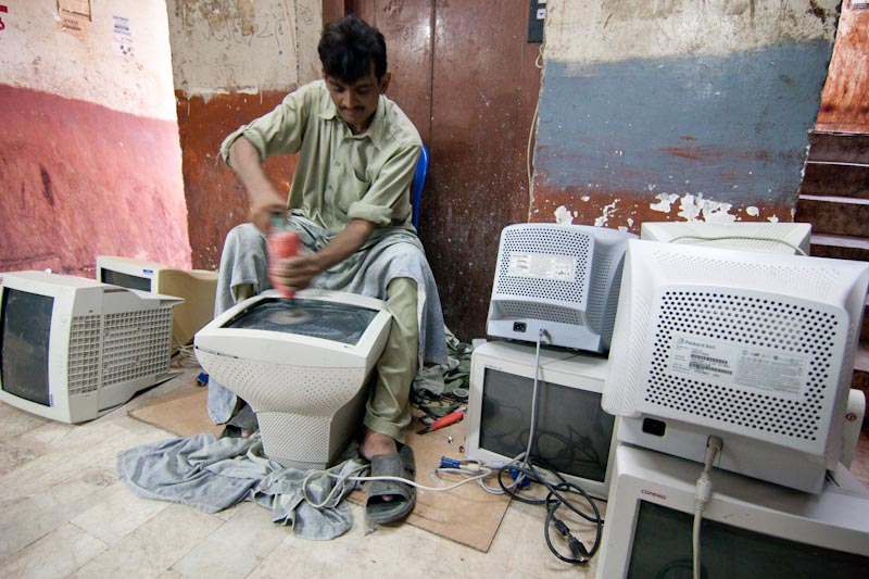 Used computer monitors imported from overseas are polished for retail at an electronics market in Karachi, Pakistan. (Photo by Alex Stonehill)