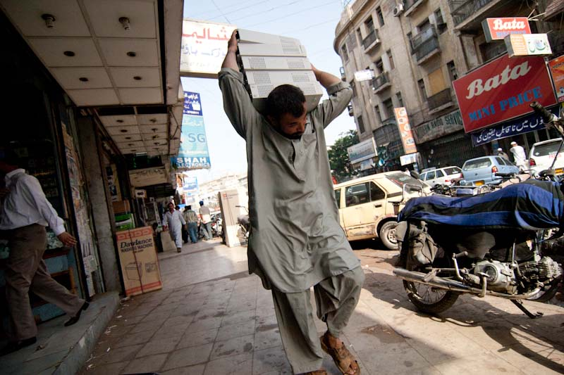 Carrying used desktop PC towers to a technology market in Karachi, Pakistan. (Photo by Alex Stonehill)
