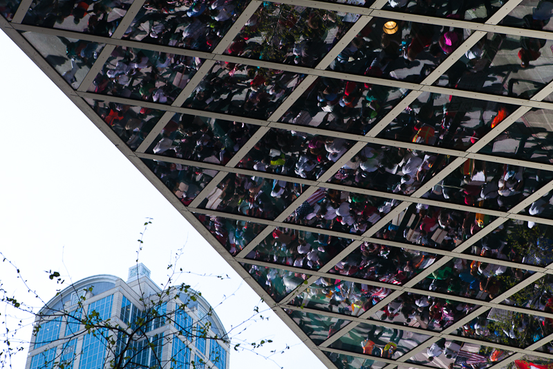 Immigration reform marchers are reflected off of the Seattle Public Library building on 4th Avenue and Madison Street. (Photo by Ian Terry)