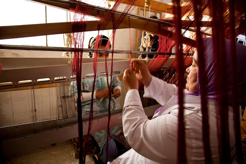 Amina Yabis, founder of the Women's Button Cooperative of Sefrou, Morocco, weaving at the loom with cooperative member Khadija La Adraoui. (Photo by Oriol Llados)