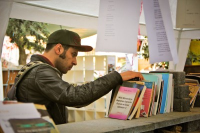 A protester browses through one of the camp's free libraries where the scope of literature ranges from Marxist theory to trashy American romance novels. (Photo by Christan Leonard)