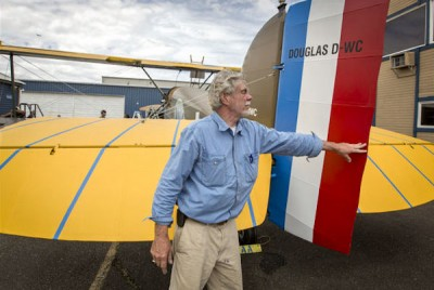 Bob Dempster pushes over the rudder of The Seattle II, a Douglas World Cruiser replica built nearly from scratch that he and his wife, Diane, intend to fly around the world. (Photo by Steve Ringman / The Seattle Times)