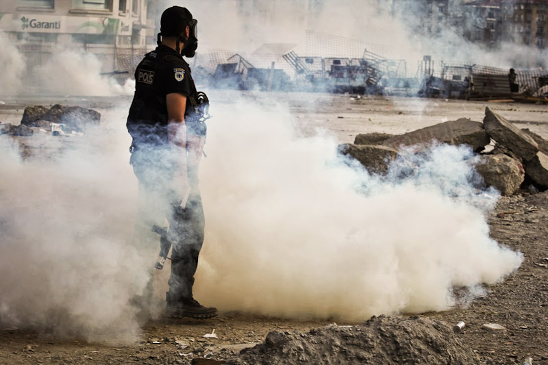 A policeman stands in a cloud of smoke during efforts to drive protestors from Taksim Square Tuesday. (Photo by Christan Leonard).