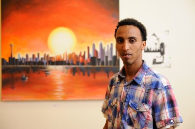 """Abraham Tesfelaise, with his painting """"Seattle"""" at the Downtown YMCA. (Photo by Coleen McDevitt)"""