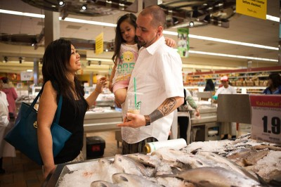 Sopheary Hermens (left) whose parents immigrated from Cambodia and Thailand, with her husband Damien and their daughter Neilah, at the Seafood City Supermarket in Tukwila. (Photo by Ian Terry)
