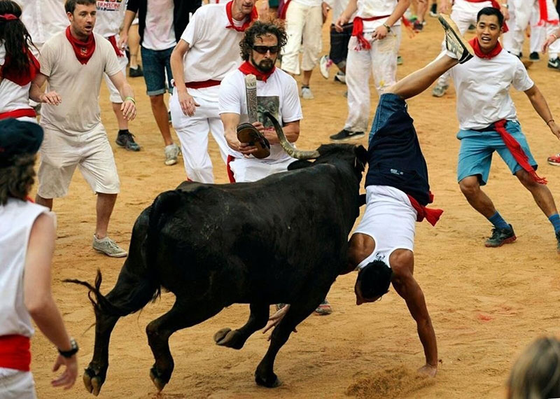 Matthew 'Griff' Griffin attempts to hang a pair of his Combat Flip Flops on the horns of a bull in Pamplona. (Photo from Reuters/Eloy Alonso)