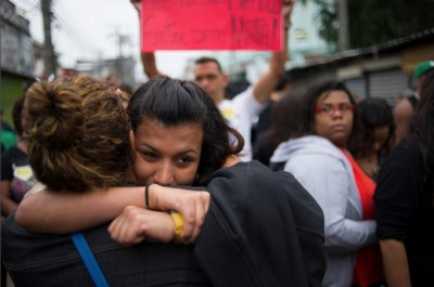 """Residents of """"Nova Holanda,"""" a shantytown in Rio de Janeirno, embrace at a memorial for victims killed in a police incursion. (Photo by Nick Wong)"""