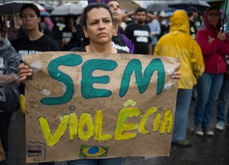 "A resident of ""Nova Holanda,"" a shantytown in Rio de Janeirno, holds a sign reading ""No Violence"" at a memorial for victims killed in a police incursion. (Photo by Nick Wong)"