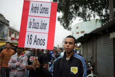 A favela resident holds a sign with the name of one of the youngest victims of a police incursion into his neighborhood, which resulted in at least 10 deaths overall. (Photo by Nick Wong)