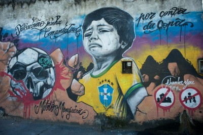 "A mural in Rio critiquing development in preparations for the World Cup in 2014 reads, ""They destroyed my community"" and ""Against the Cup."" (Art by Metro Mangueira, Photo by Nick Wong)"