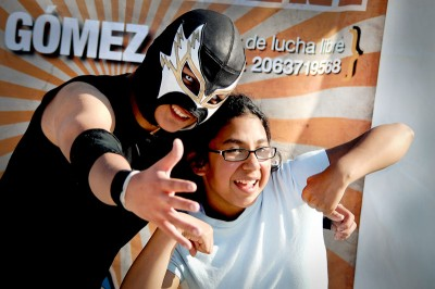 """Luchador Mike """"El Sonico"""" Jacinto poses with a fan in 2012. (Photo by Latino Cultural – Mauricio Ayón / Seattle Department of Neighborhoods)"""