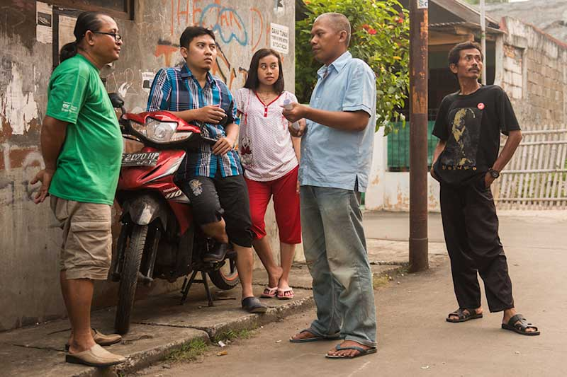 Anissa (center) and her husband (second from left) with fellow workers and union leaders in a Northeast Jakarta neighborhood near the factory where they work. (Photo by Branden Eastwood)
