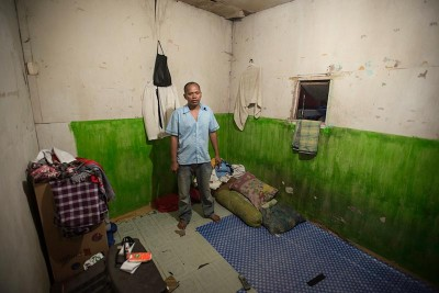 "An Indonesian garment factory worker in his one room apartment. Prevailing wages in the garment industry are rising, but still only make up 22% of an estimated ""living wage"" in Indonesia. (Photo by Branden Eastwood)"