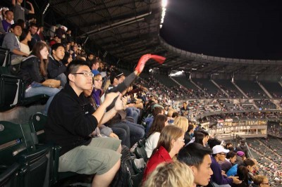 Wenbing Zhang, 19, of Beijing, China, an incoming freshmen at UW, celebrates a Mariners home run with other UW international students. (Photo by Alex Stonehill)